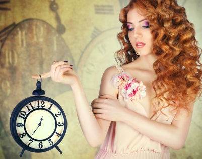 Young beautiful girl holding a large wall clock..against the bac